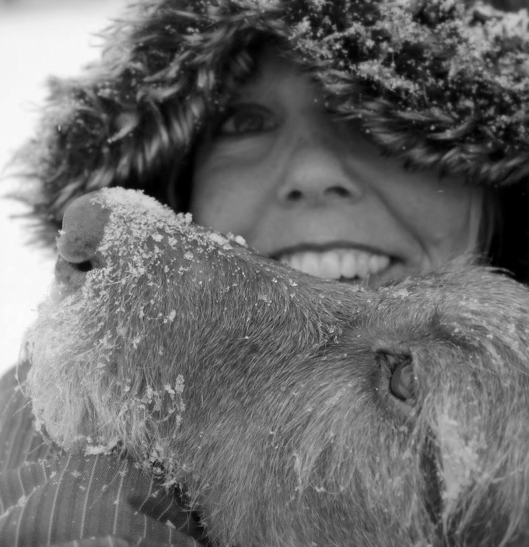 Woman with faux fur hood and dog resting head on her shoulder. Snow covers the dogs muzzle.